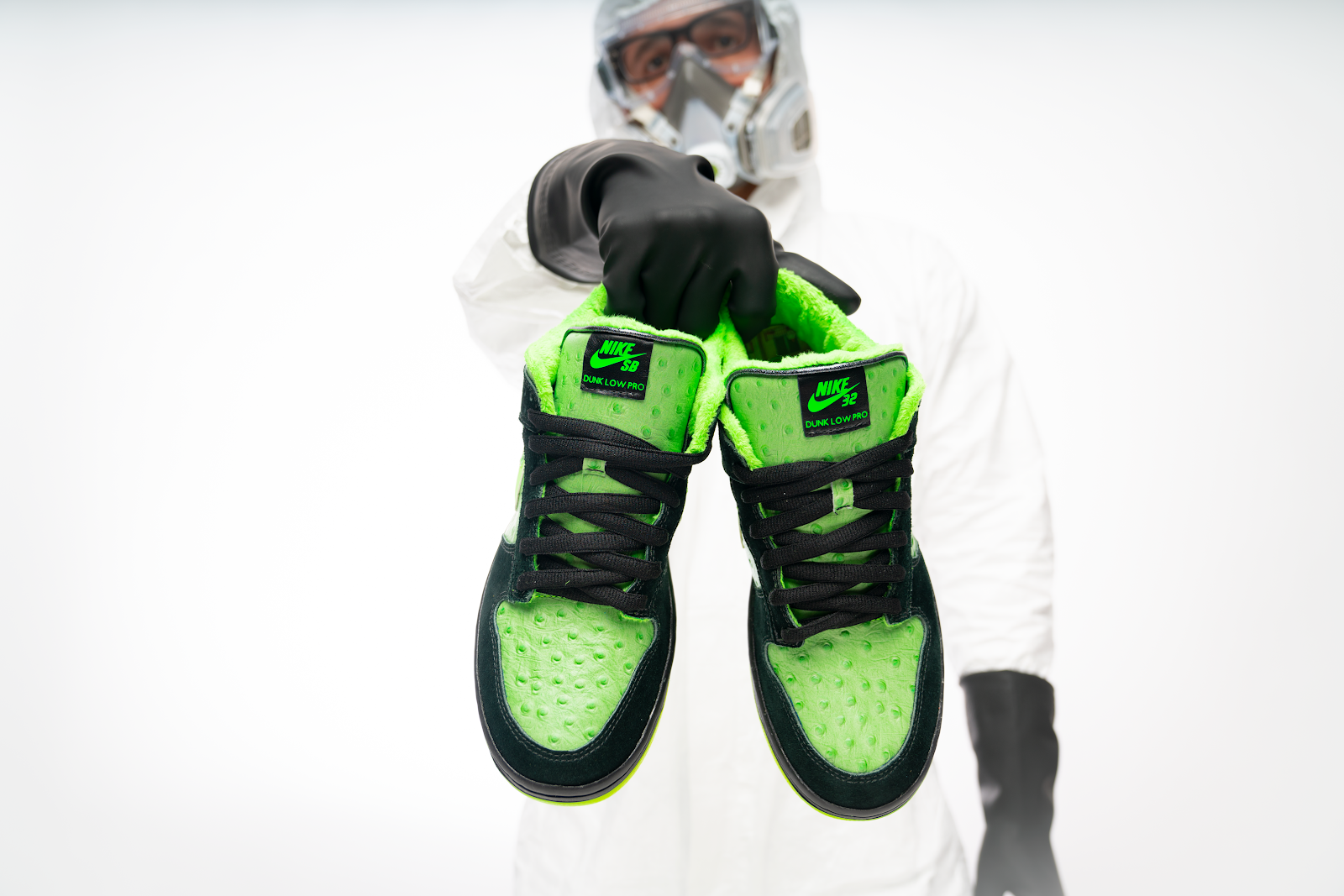 Barrios wears a hazard suit, face mask, and gloves while holding a pair of black and neon-green low-top Nikes.