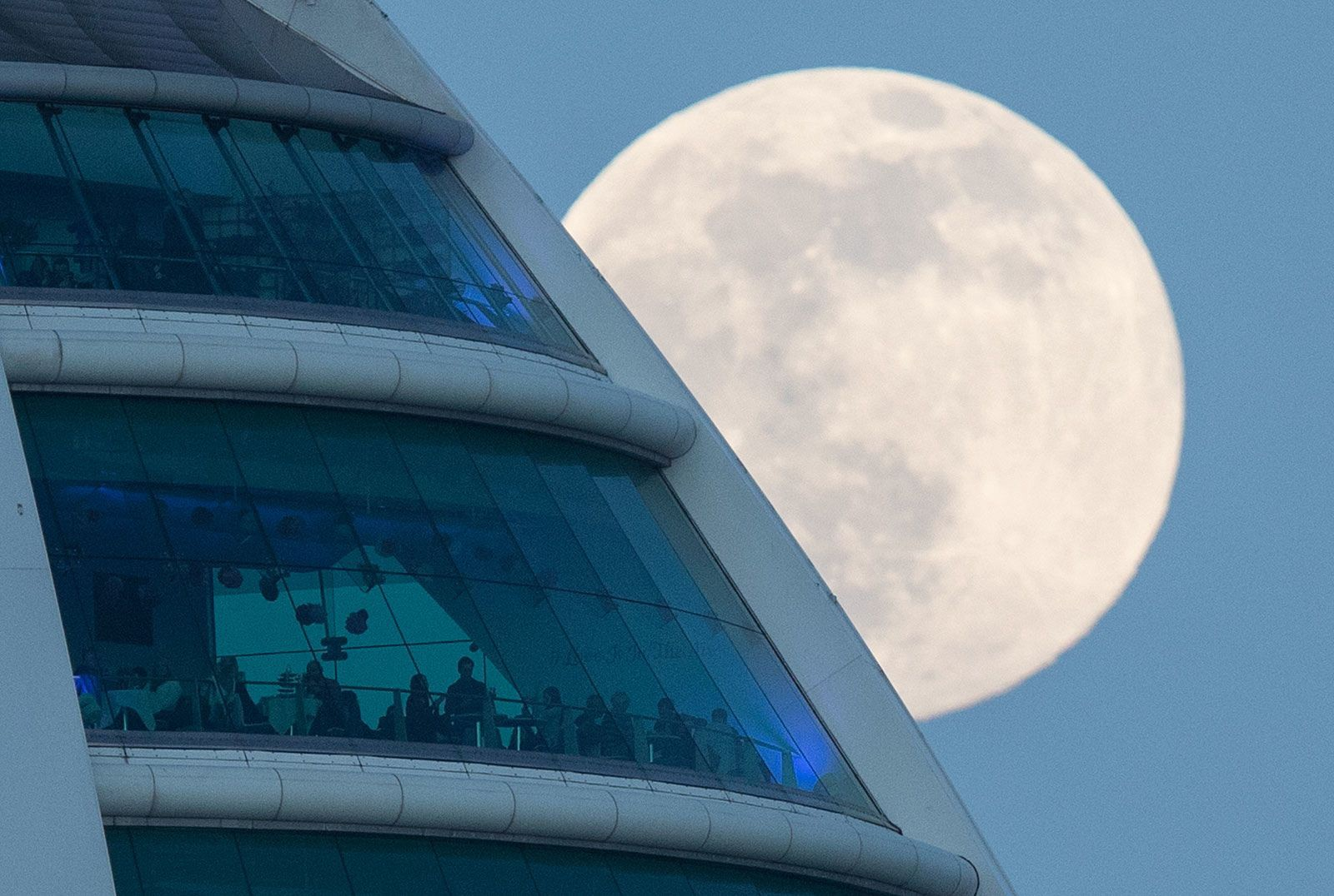 The Winter Moon rises behind Spinnaker Tower in Portsmouth England. Image by Andrew Matthews/PA Images via Getty Images