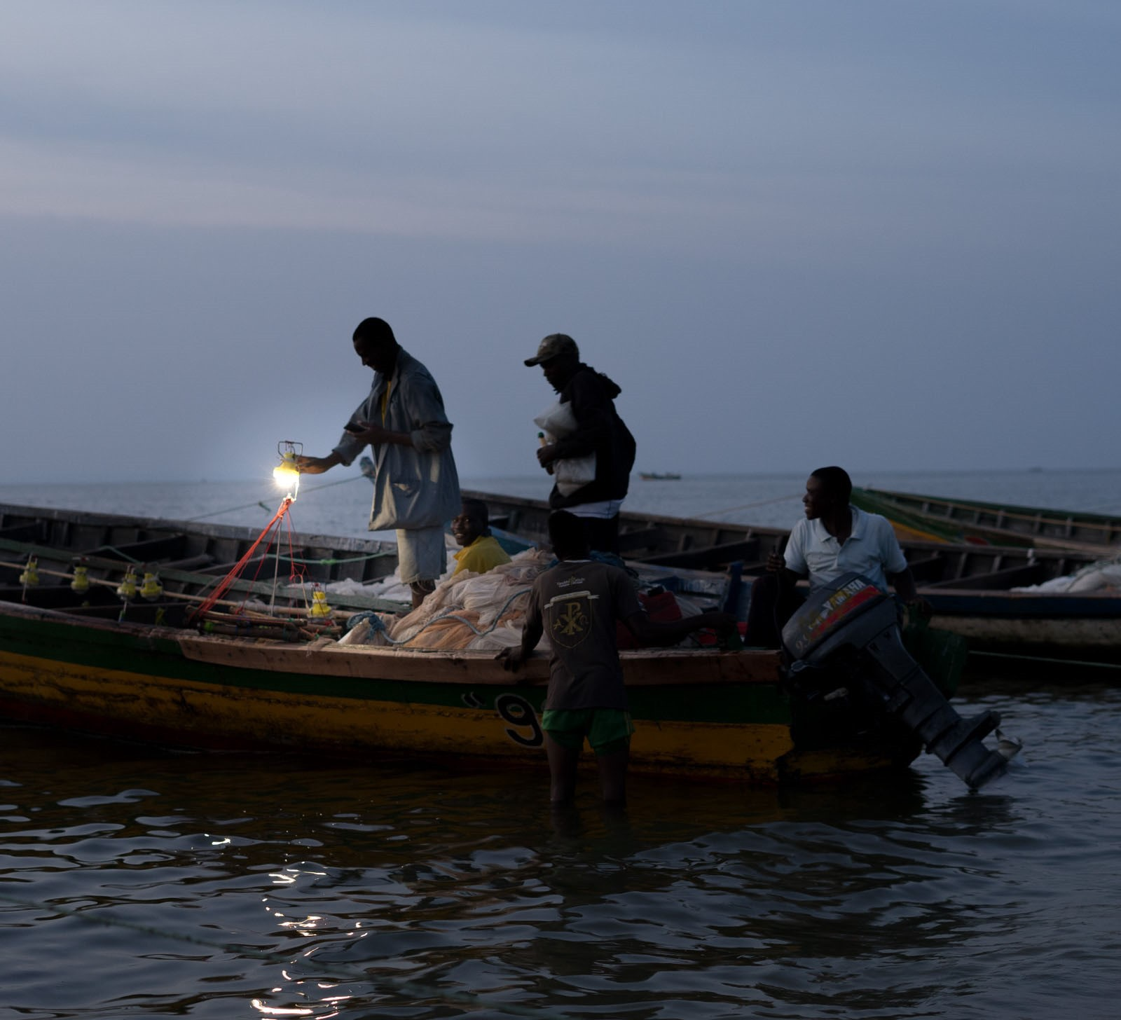 Night fishers charging solar-powered fishing lights to prepare for a night out on Lake Victoria.