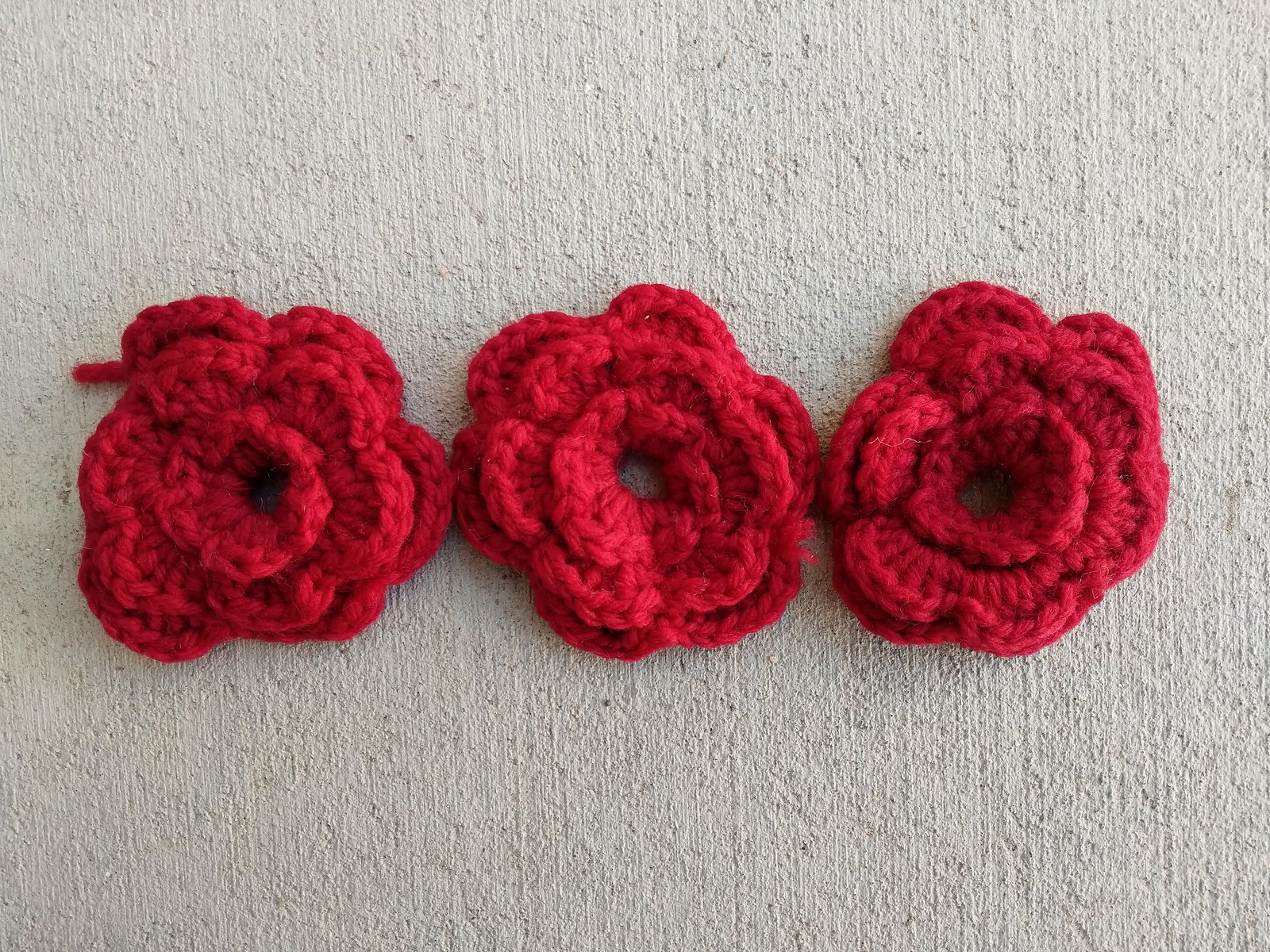 Three red crochet flowers