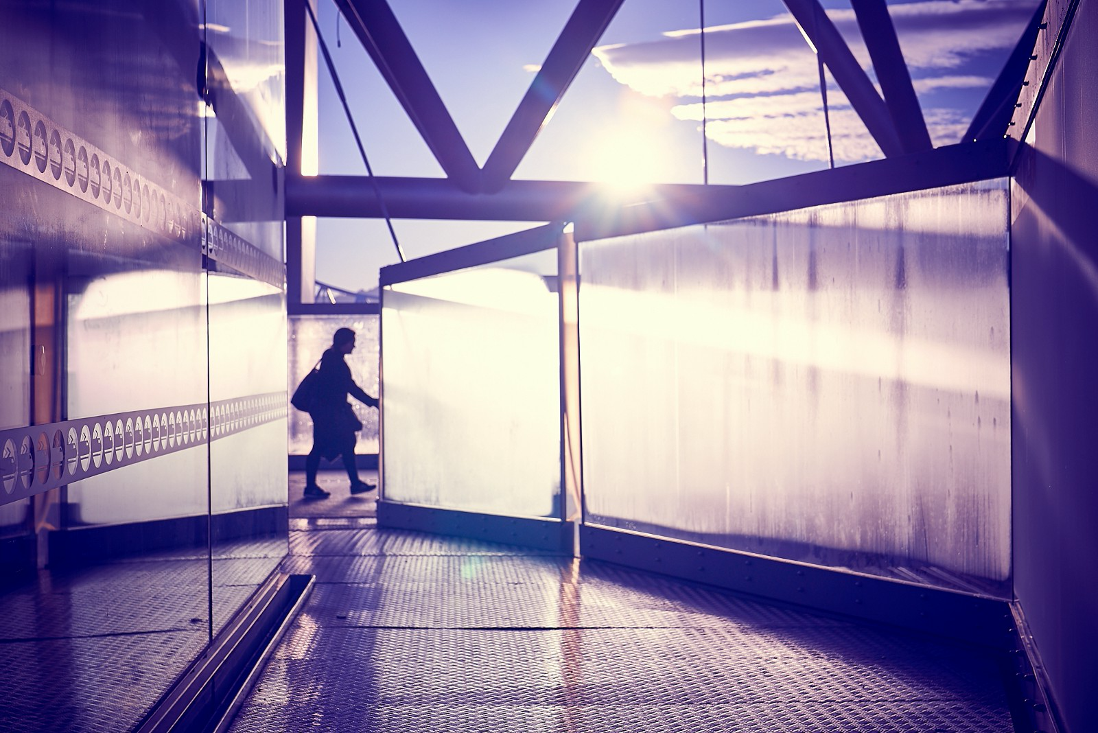 Image: the silhouette of a woman with a big handbag passing between opaque sheets of glass on a pedestrian bridge in Oslo