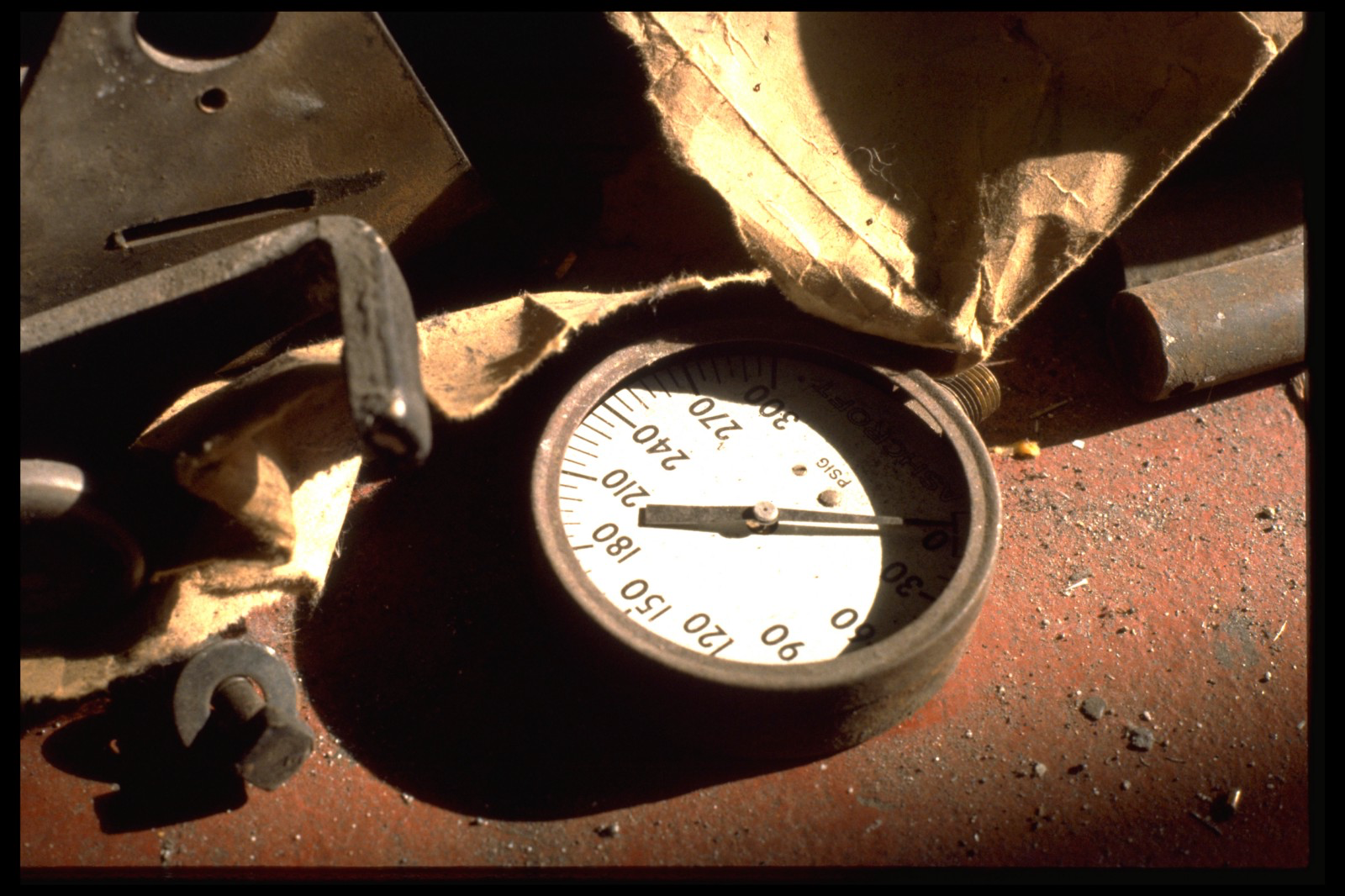 broken mechanical pressure gauge and other random debris in close up on a red cement shop floor