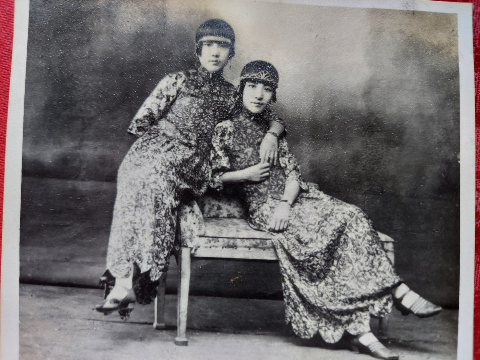 Black and white old photo of two young Chinese women lounge posing in long, floral gowns, 1910s/1920s style bob haircuts.