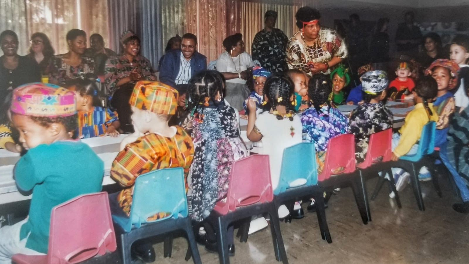 Image Description: Photo of classmates dressed in colorful traditional African attire gathered at the table