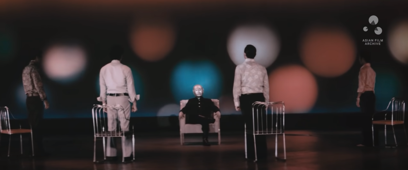 Seated in a chair, the main antagonist, wearing an iron mask, is scanning his men. The background is black with colored spots