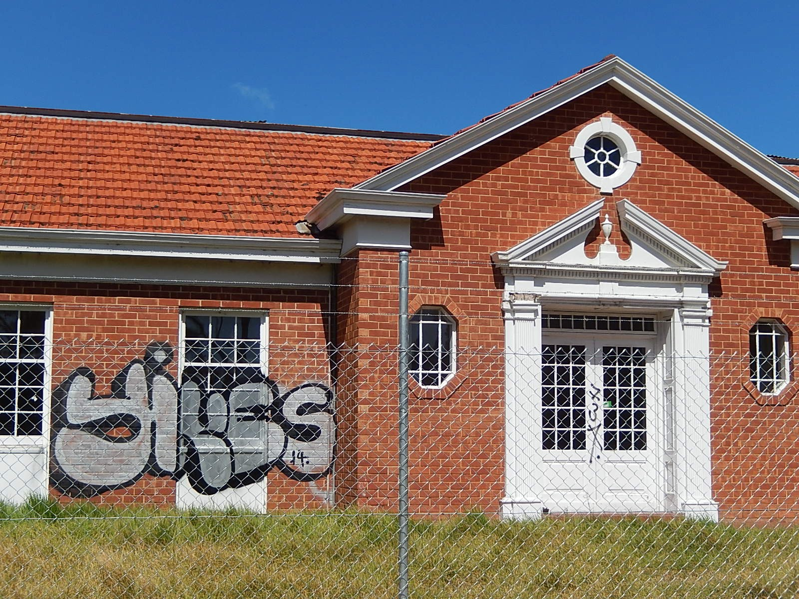 "A dilapidated one-story building with ""yikes"" graffittied over a window, behind a chain-link fence."