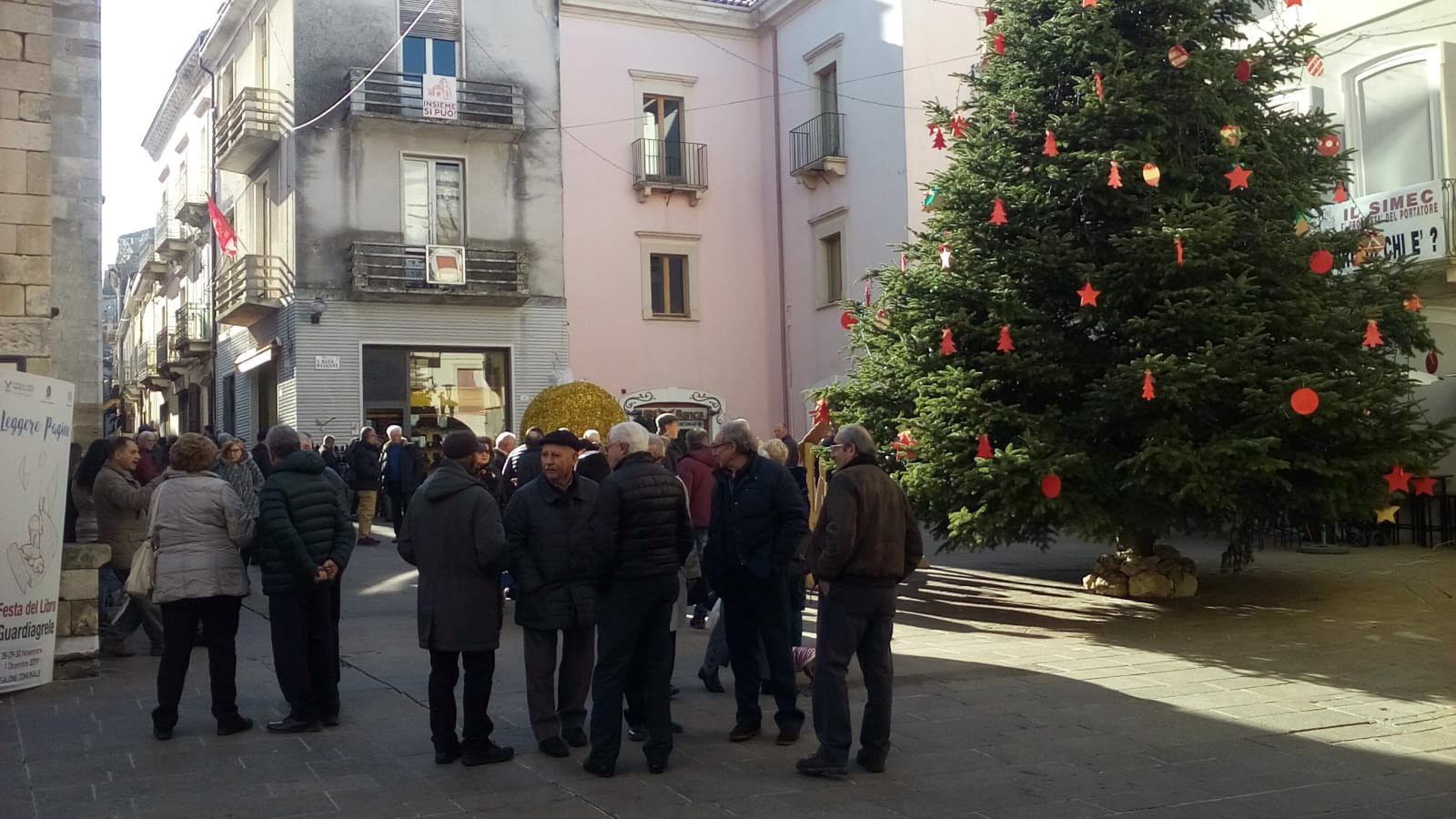 A group gathers on Sunday morning by the community Christmas tree in Guardiagrele's main piazza.