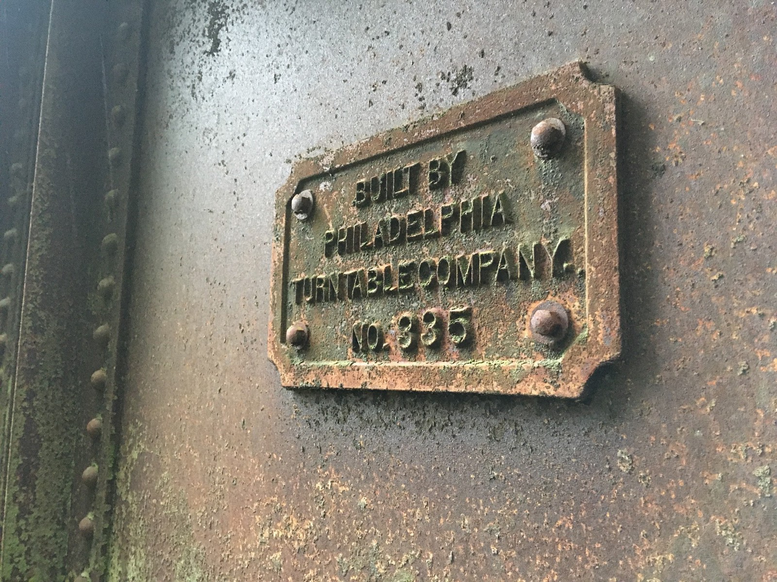 A builders plate attached to side of rusty turntable