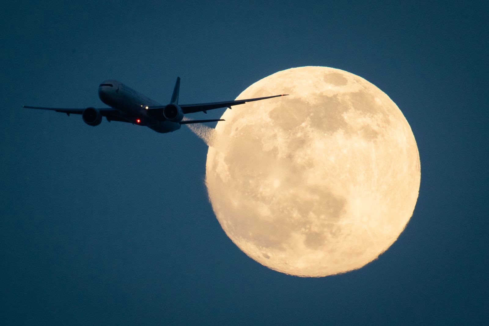 A plane passes in front of the moon as seen from London. Image by Aaron Chown/PA Images via Getty Images
