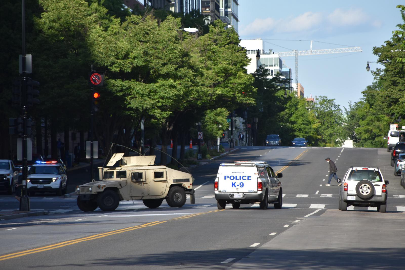 Tan military humvee with police vehicles on the streets of Washington, D.C.