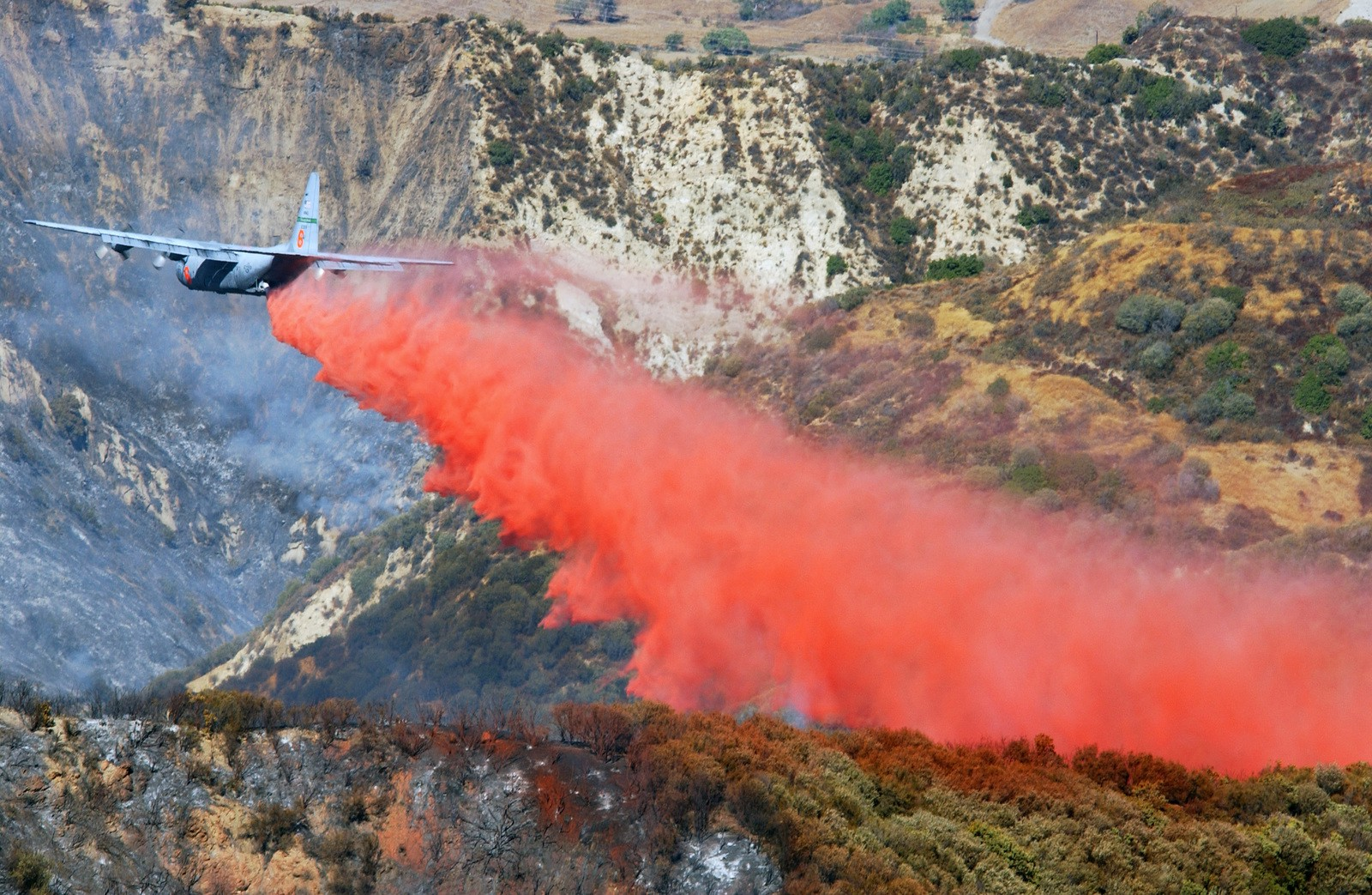 Plane dumping water on wildfire in california