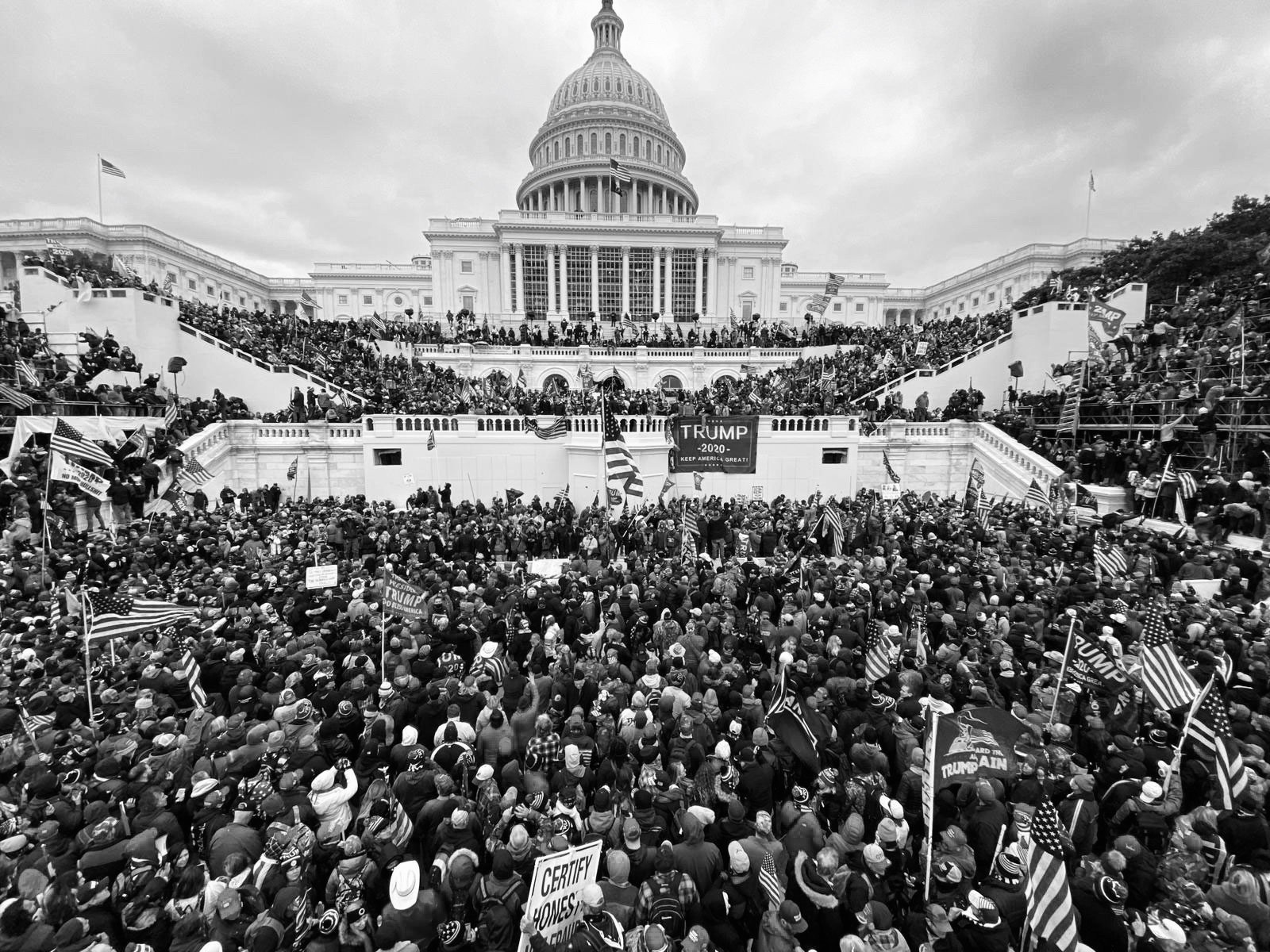 This photo shows the U.S. Capital as thousands of President Trump supporters, rioters, and insurrectionists gather to protest Biden's election. At this point in the protest, they have breached the barriers, and are climbing over the steps. Some have made their way into the building, via breaking down doors and windows.