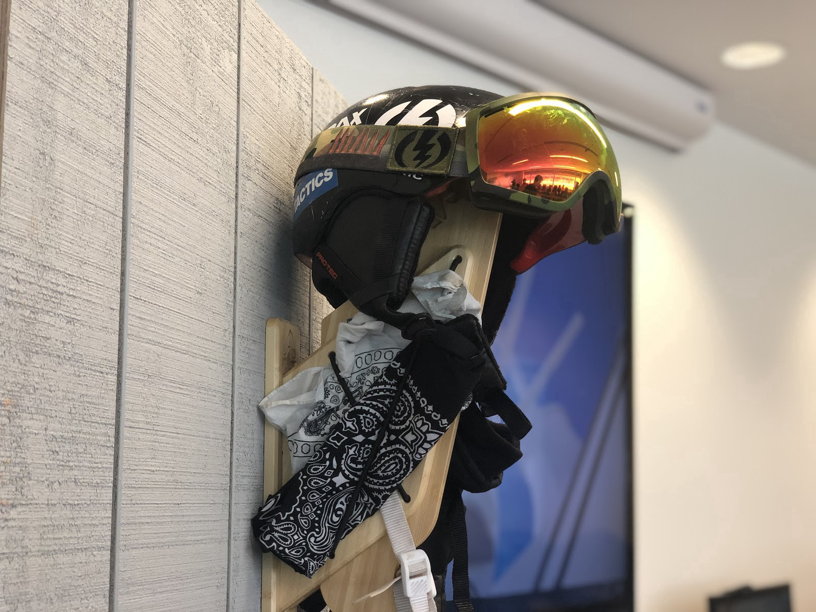 The Strax Rack hanging on a false gray wall with a snow helmet, goggles, and bandanas hanging it from it to show how it works