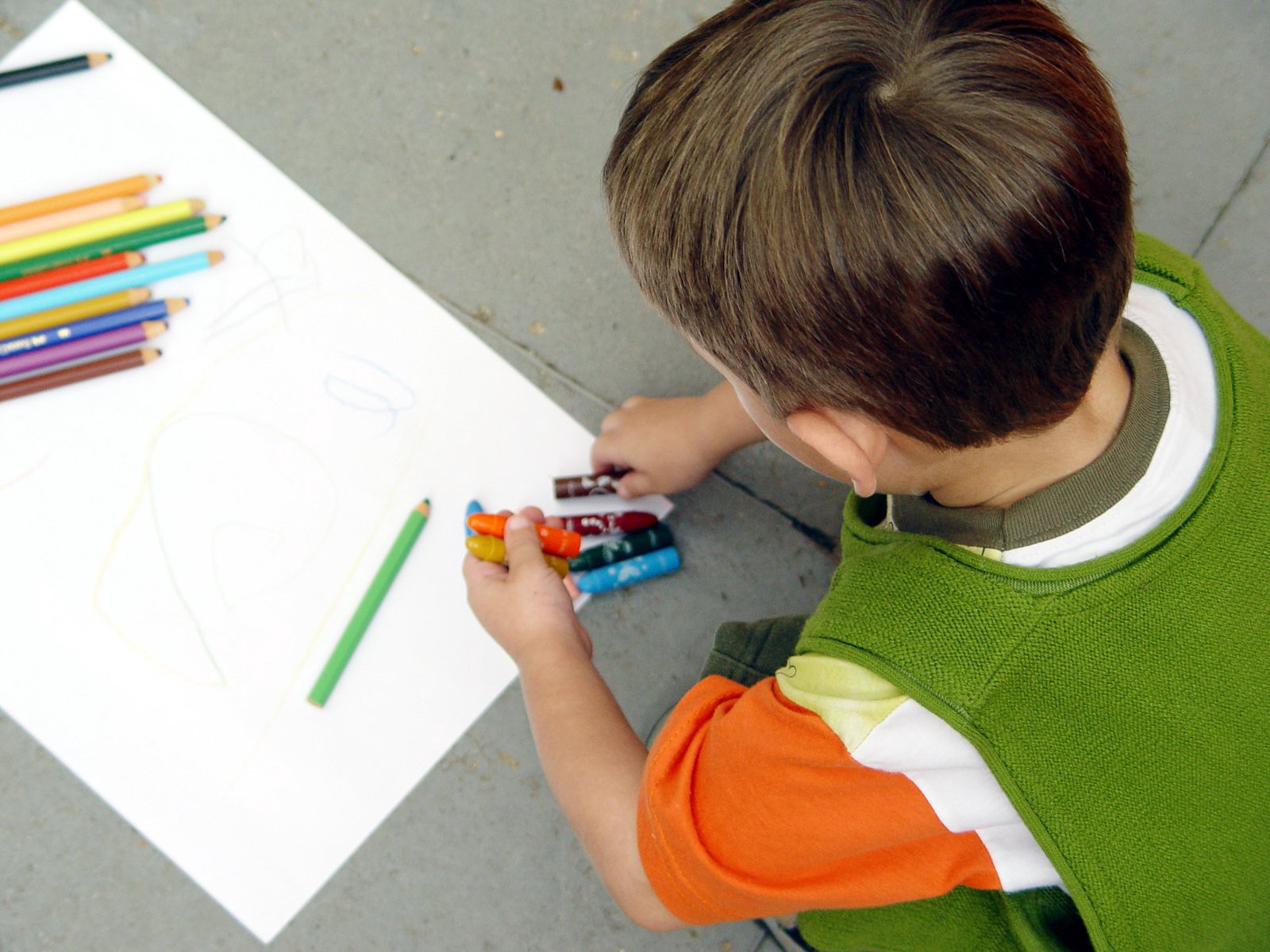 Paned shot of a child setting his pencils upon a hald drawn sheet of paper.