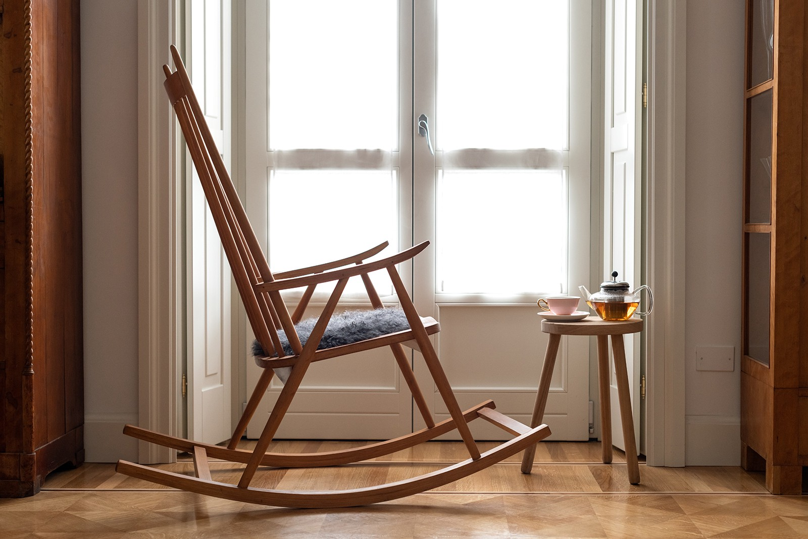 Photo of a rocking chair in front of a window with a small table with tea on top.