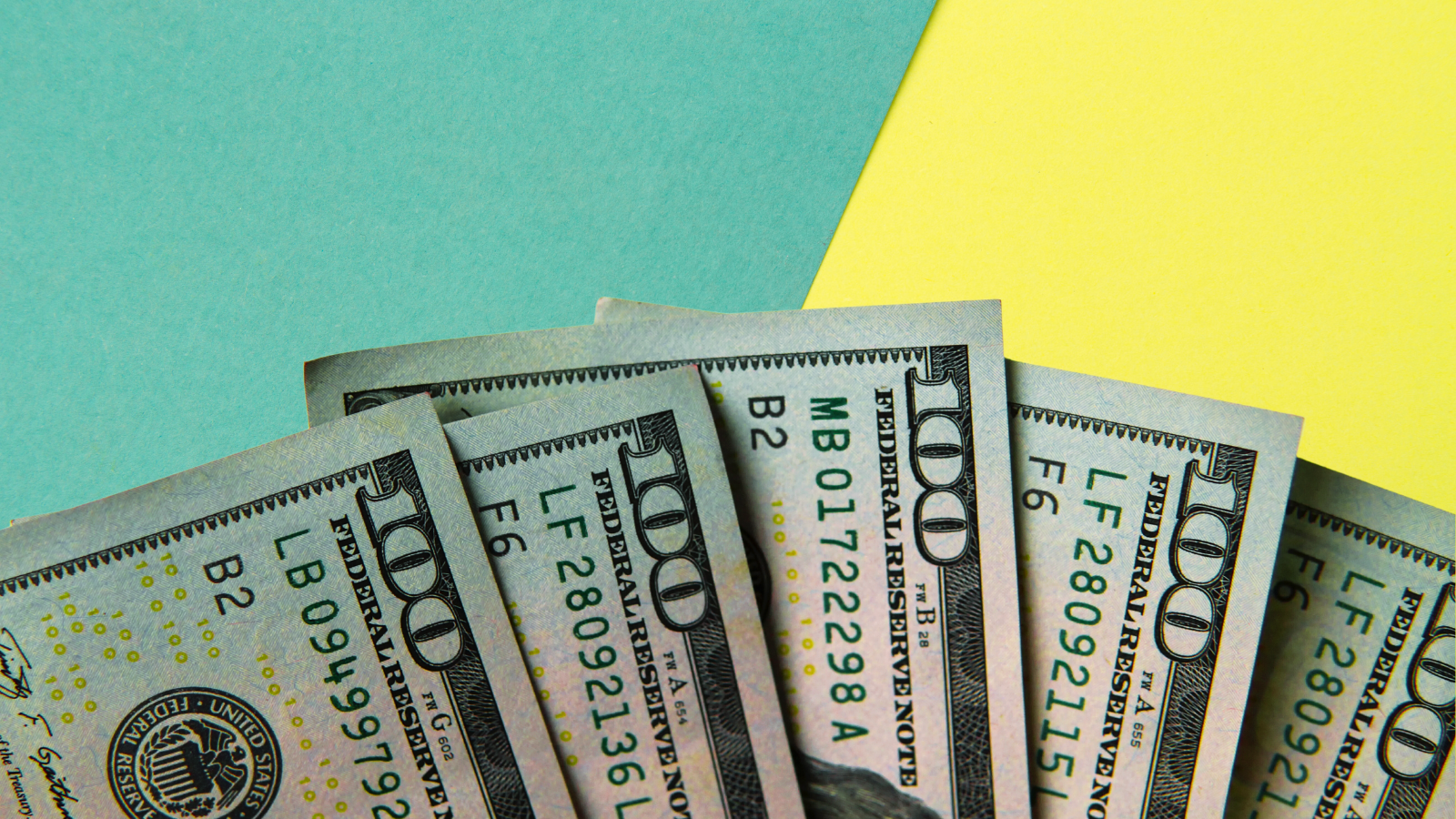 Mint green and yellow construction paper background with five $100 bills superimposed on top in a fan pattern