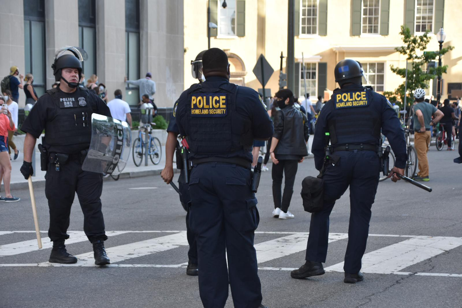 Police officers in helmets holding batons and shields on 16th Street in Washington D.C.