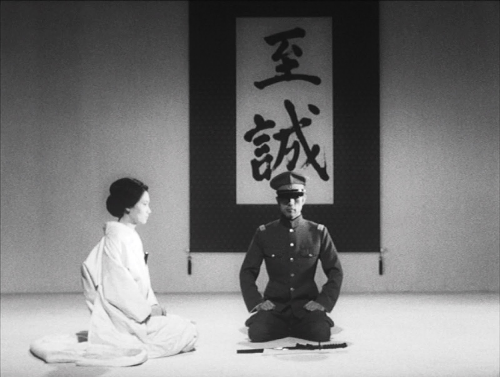 Mishima, in a military attire is leaning in front of a Japanese scripture. His wife is sitted to his right, in a white dress.