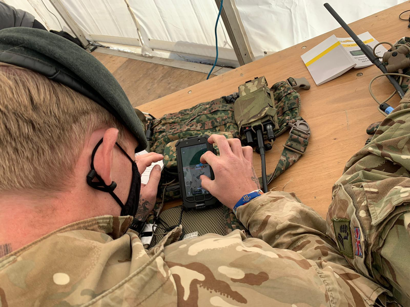 Soldier looking at a small mobile device and relaying that information back to other soldiers