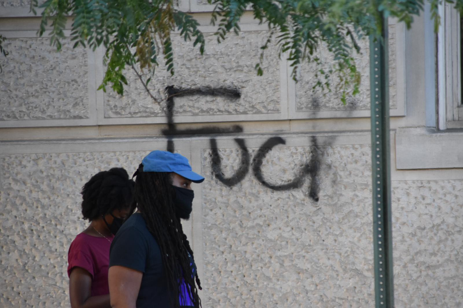 """Two people wearing masks walk by a wall with graffiti of the word """"Fuck"""" in Washington, D.C."""