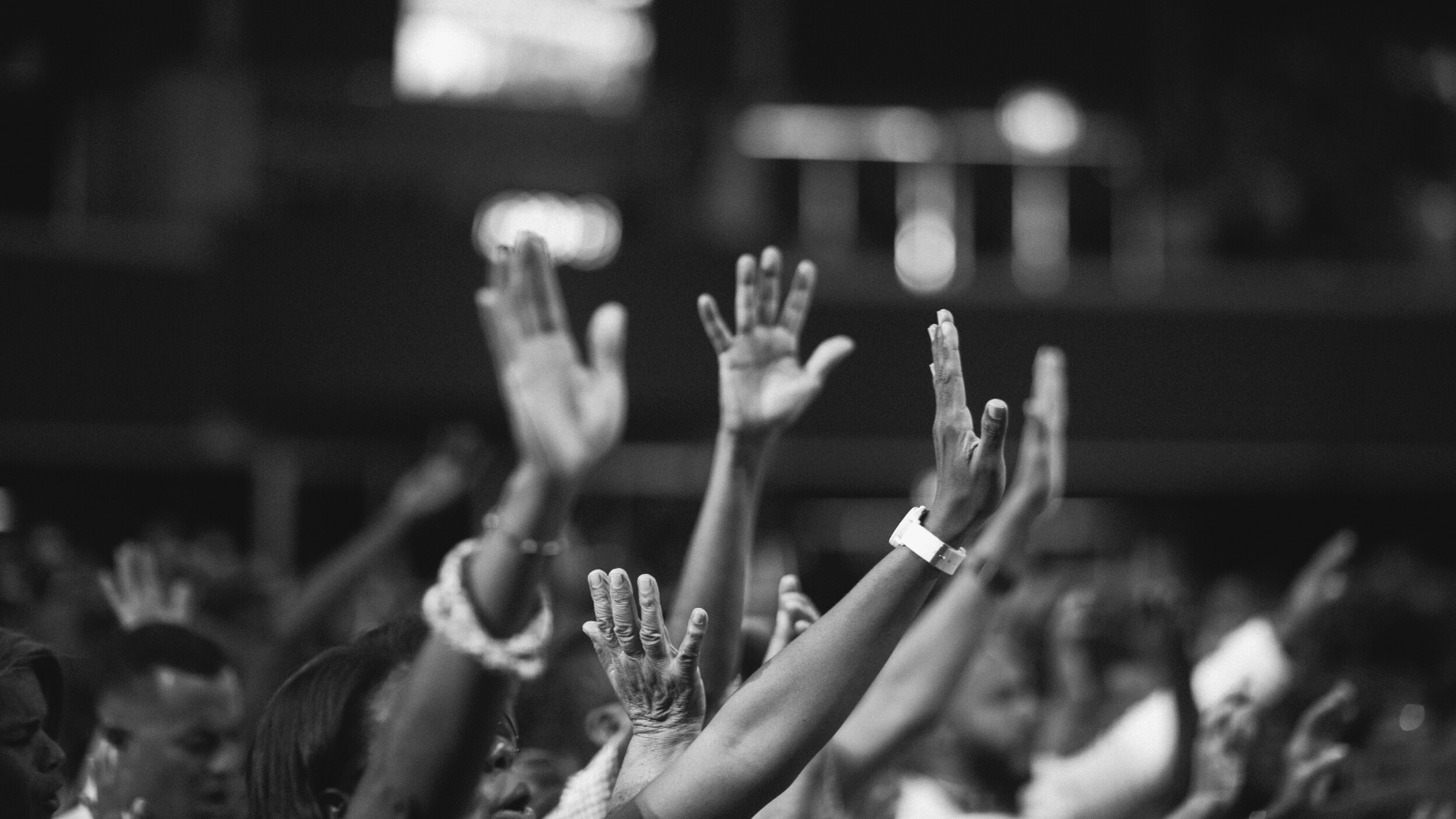 Grayscale image of people holding up their hands
