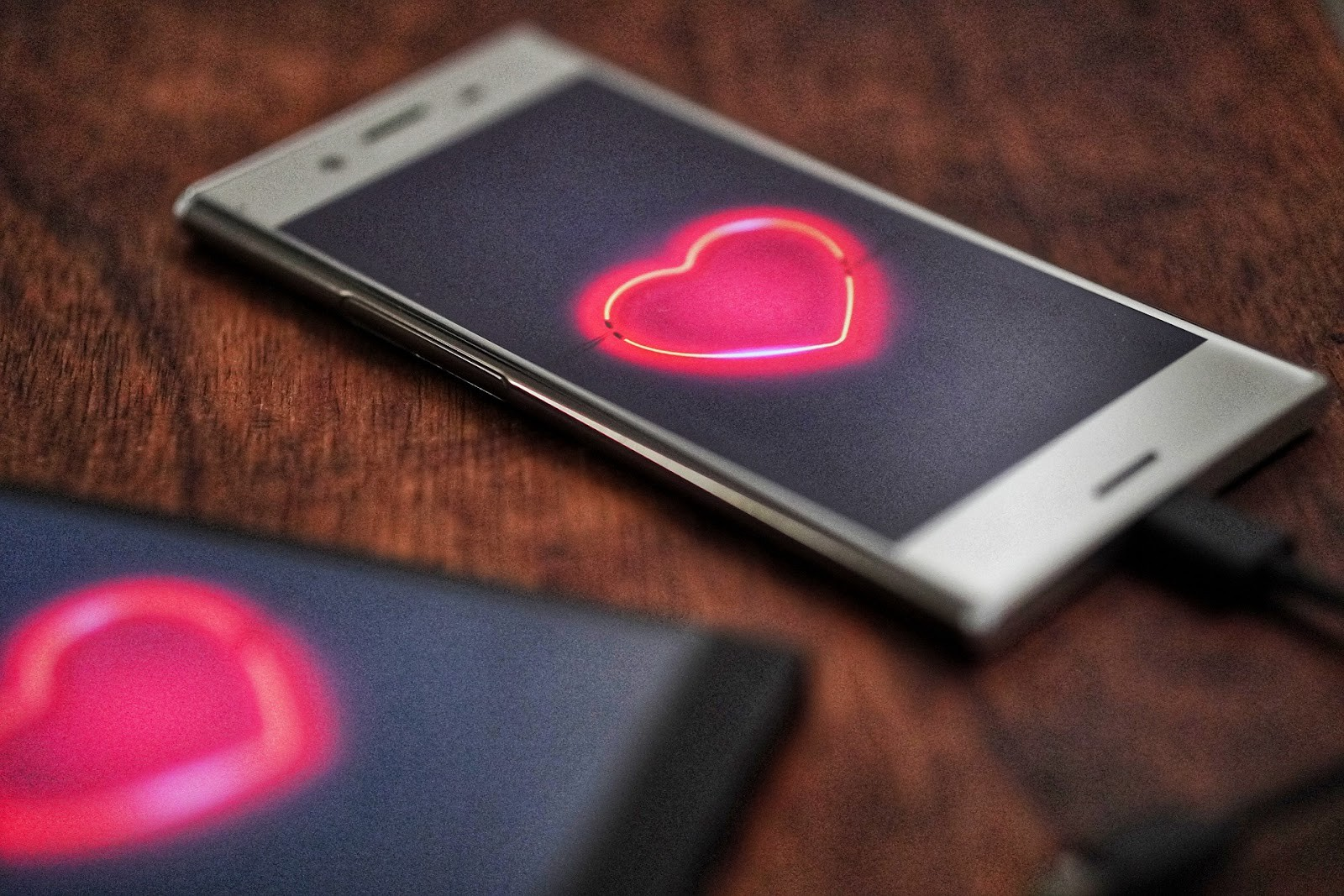Two smartphones displaying bright red hearts.