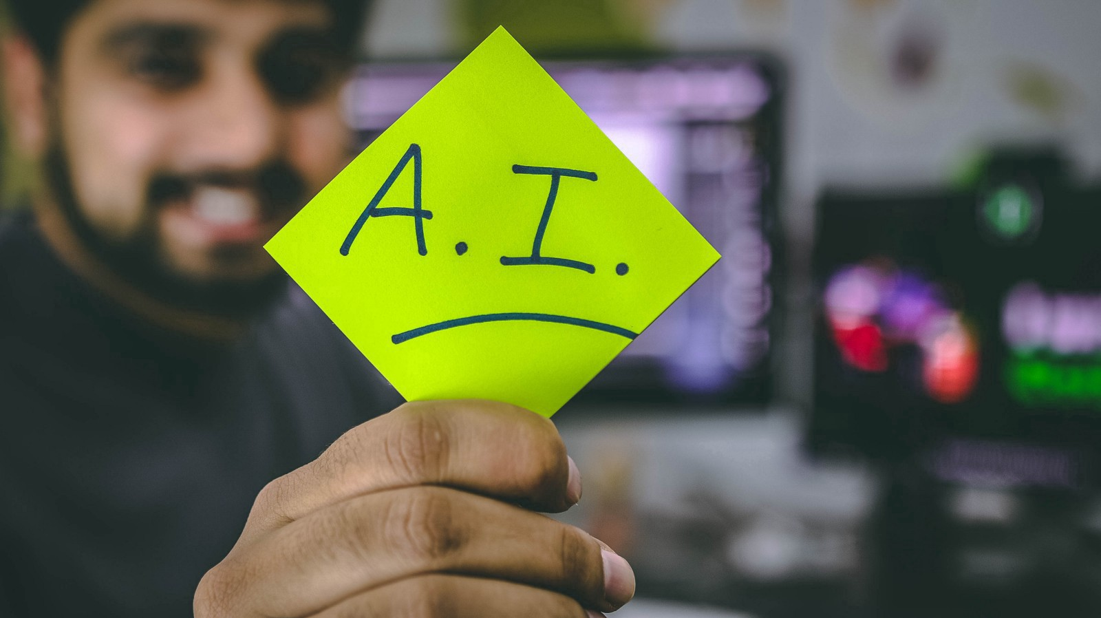 "A man holding a paper ""A.I"" text on it"