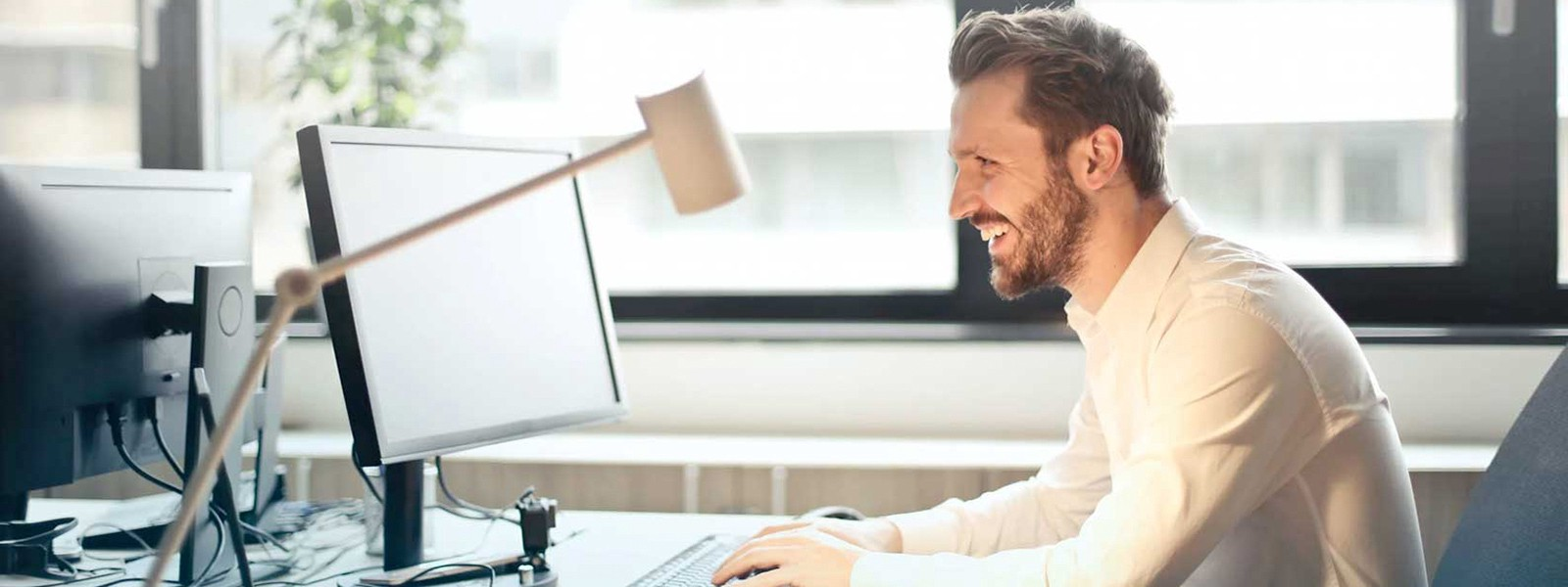 Man sitting at his desk smiling while using his computer