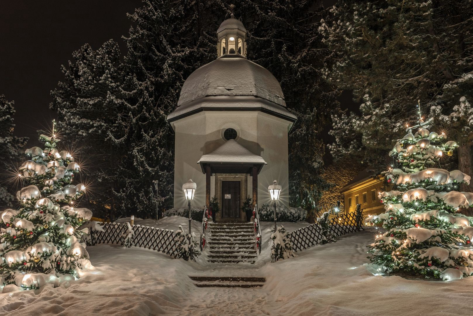 Silent Night Chapel at night, lit by string lights and lanturns