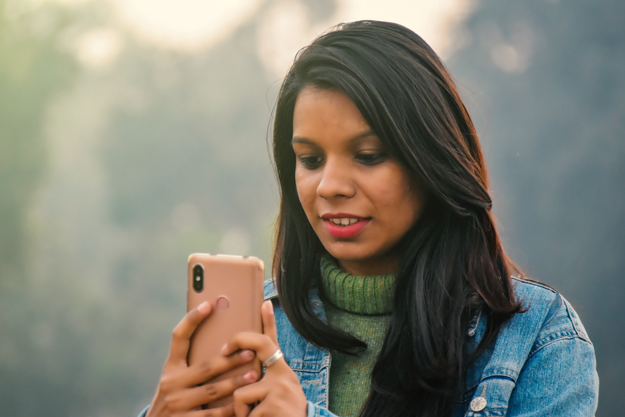Woman looks at her phone with a pleasant expression