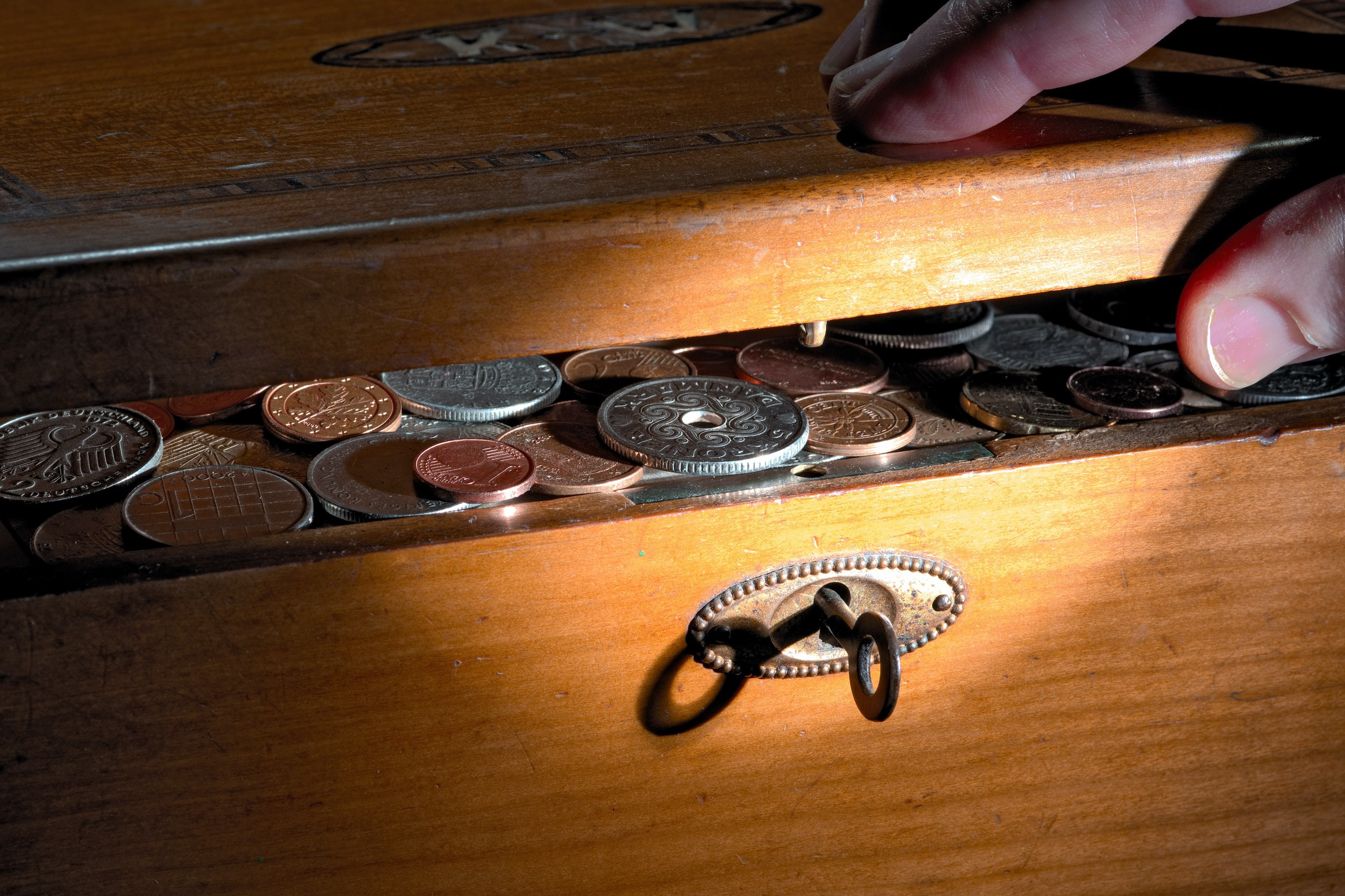 Fingers opening a wooden box with coins inside, like treasure