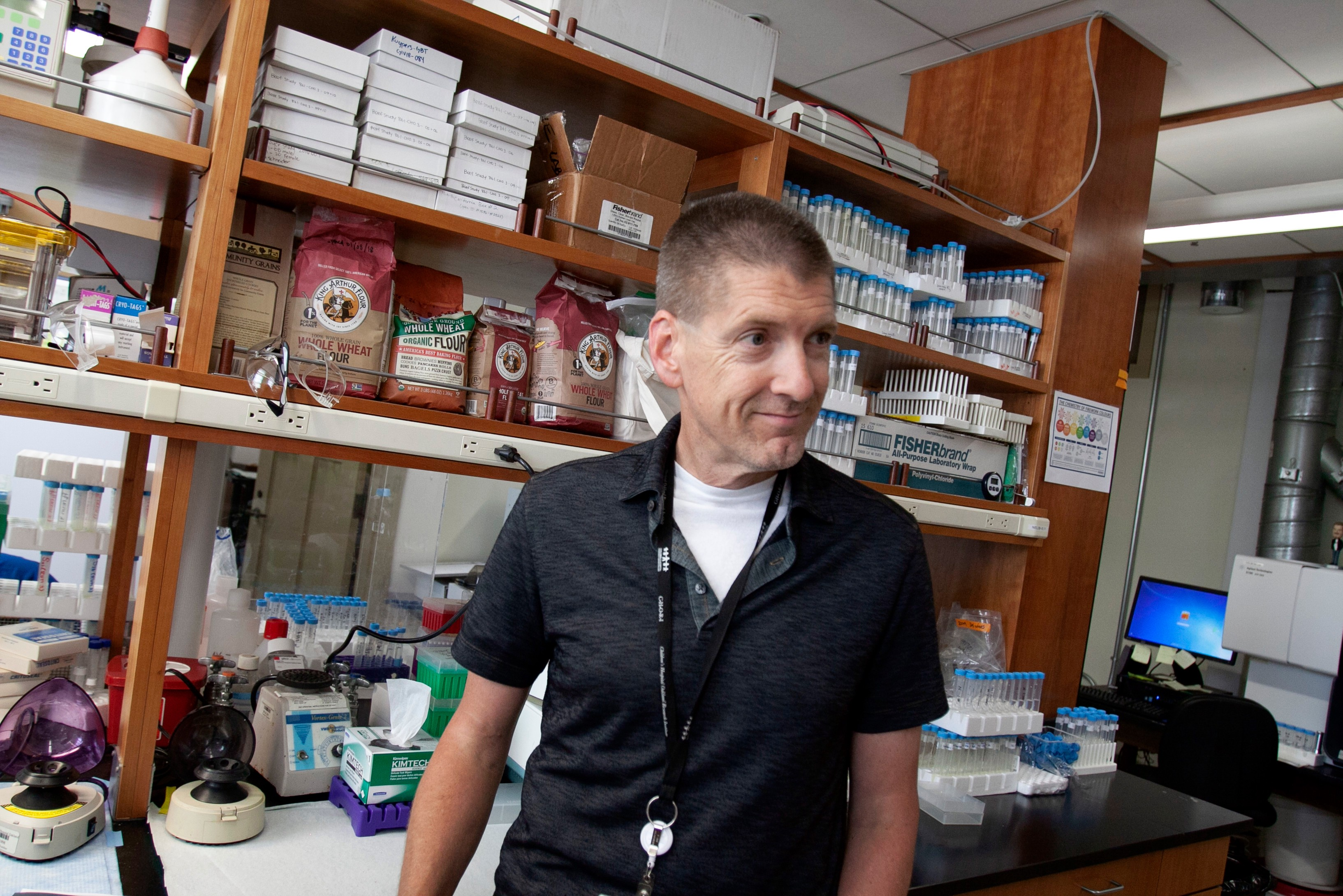 Dr. David Killilea standing in a laboratory, in front of a desk with shelves with Bob's Red Mill flour and testing equipment.
