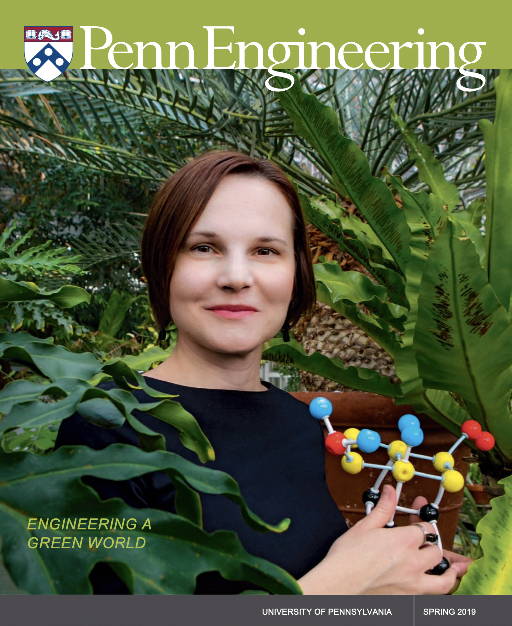 Aleksandra Vojvodic stands in a greenhouse, holding a model of a catalysis reaction.
