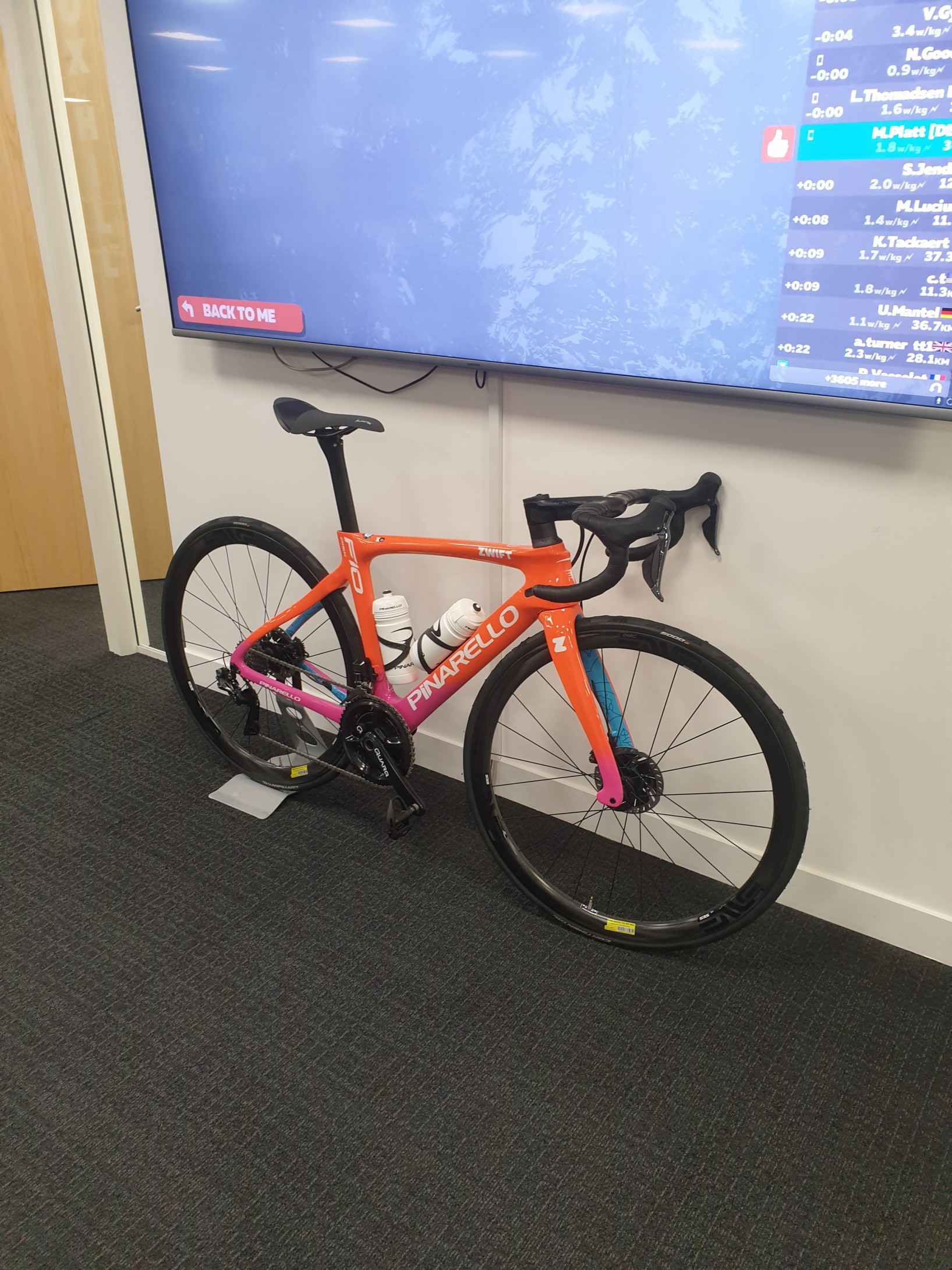 An orange road bike underneath a large wall-mounted TV in an office