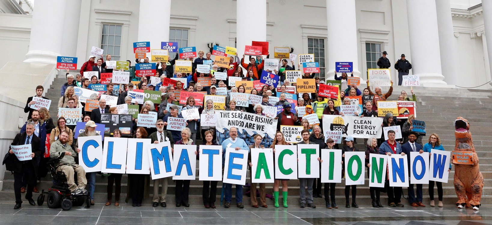 A crowd holds up signs expressing their support for climate action and 100% clean energy.
