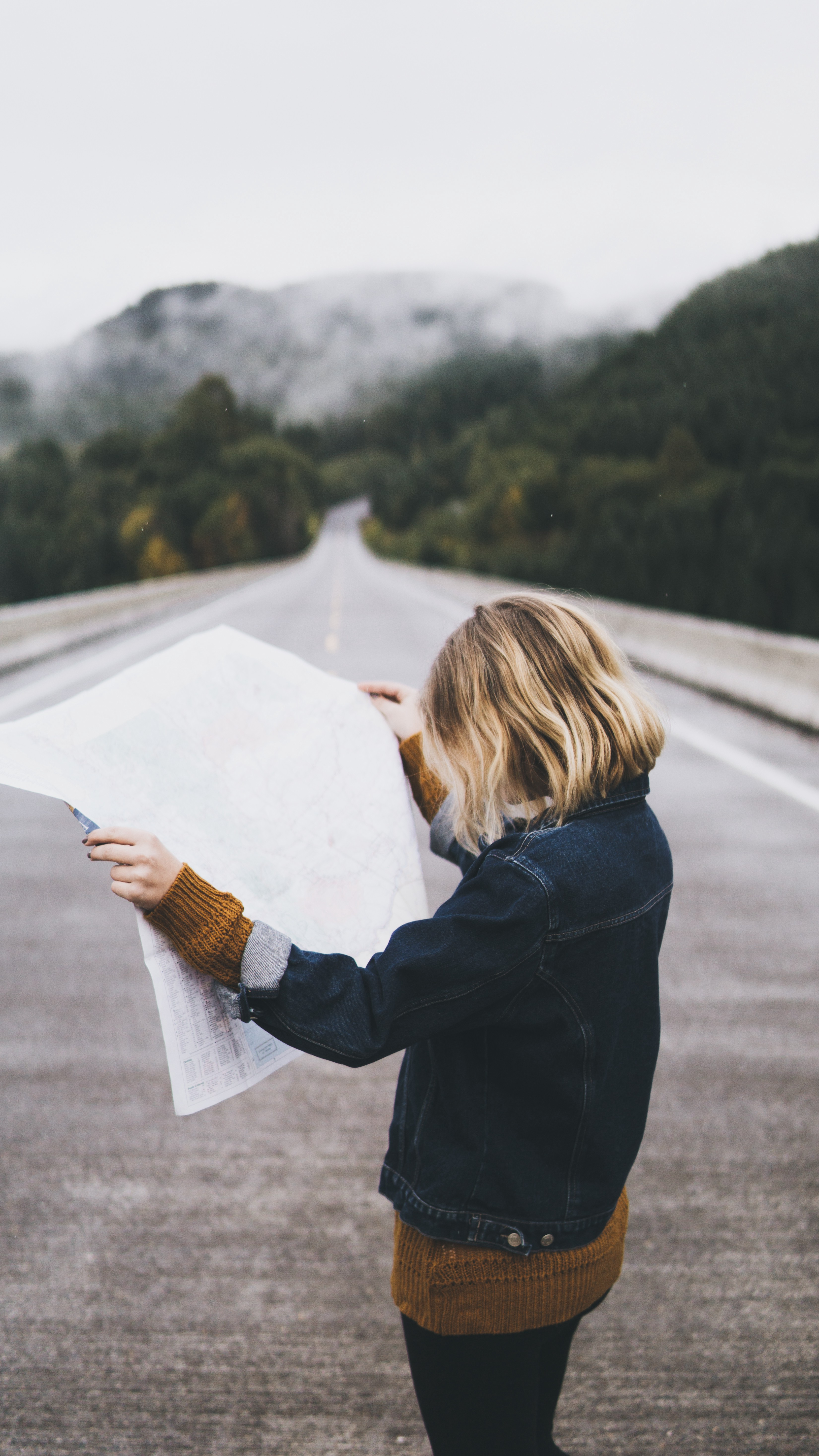 A person with short blonde hair looking at a large blank piece of paper in the middle of the road.