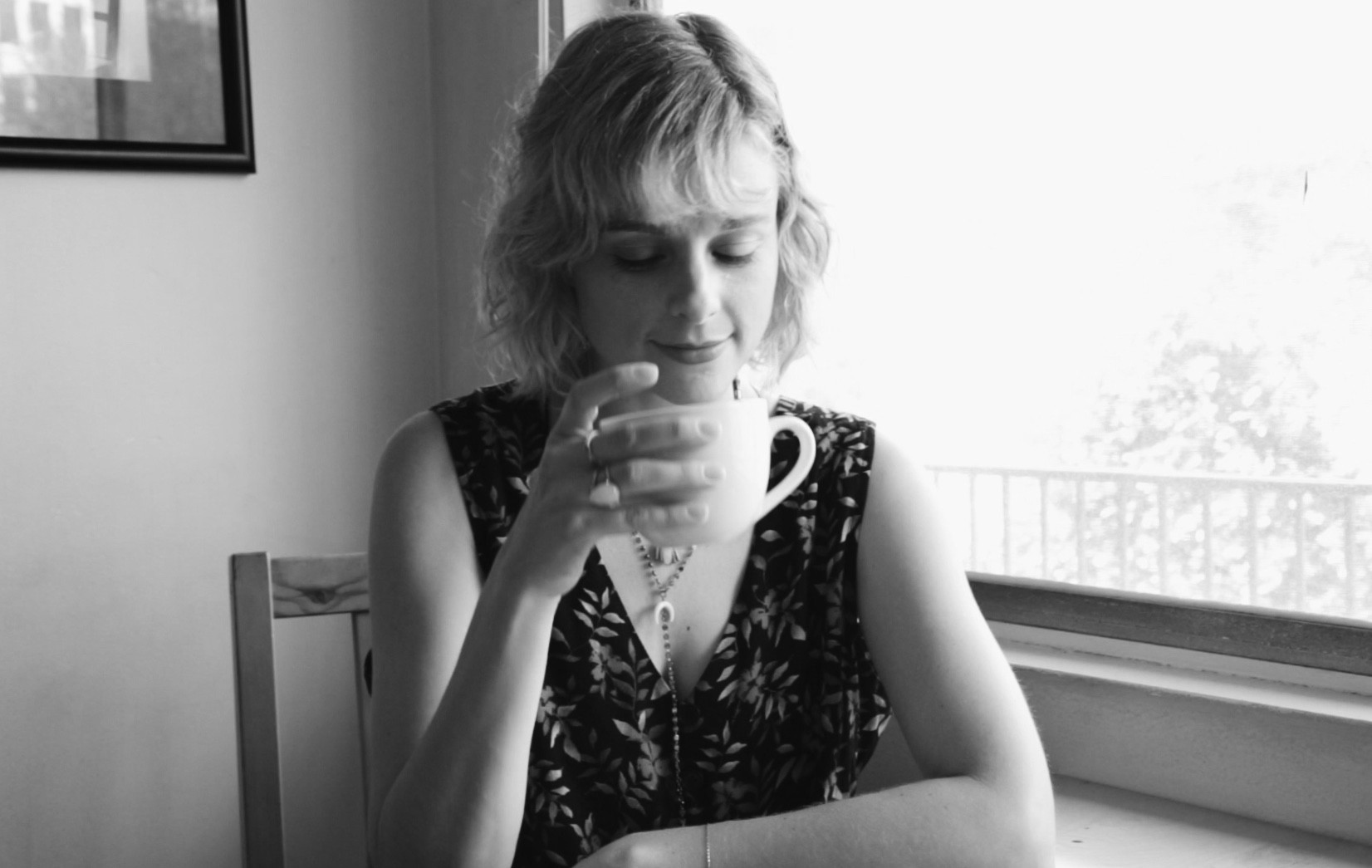 A black and white photo of a woman drinking a cup of coffee by a window in her home.