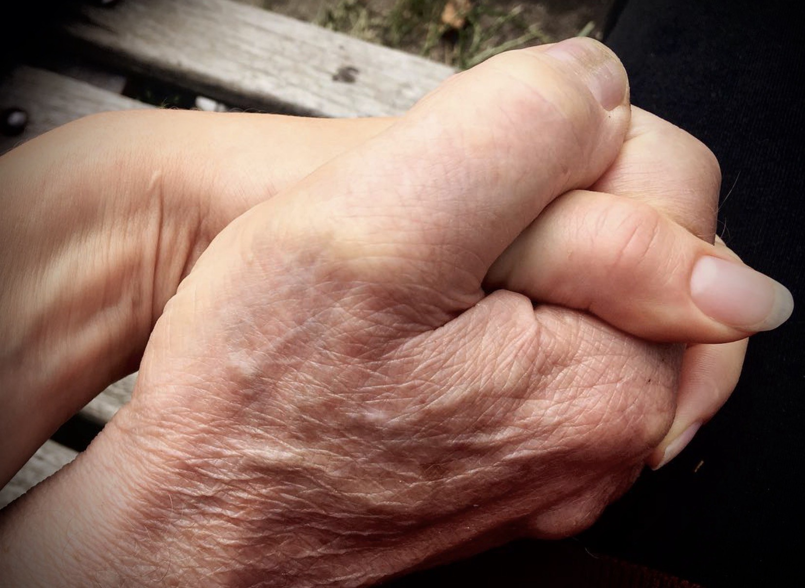 Young woman's hand holding her father's bigger, ageing hand