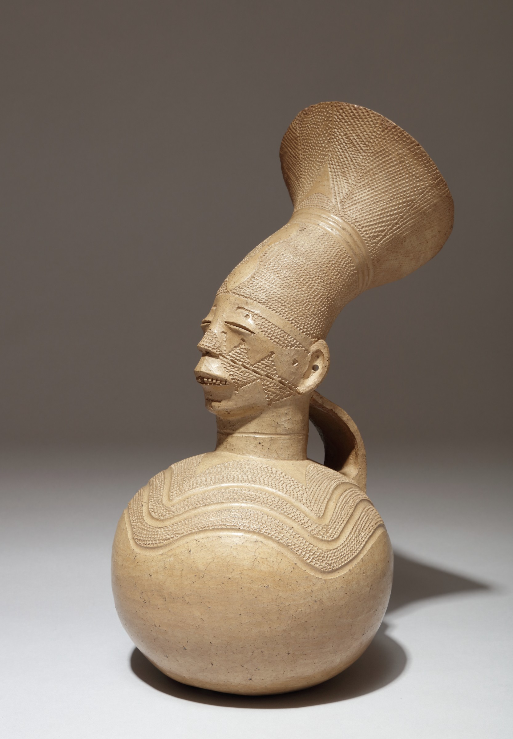 Terra-cotta vessel featuring a bust of a woman wearing a traditional, sculptural Mangbetu hairstyle known as a tumburu.