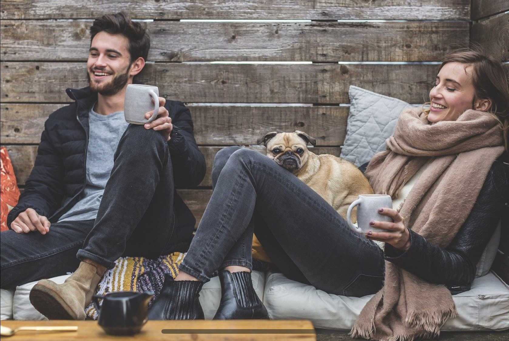 A smiling couple drink hot drinks and enjoy each other's company with a cute dog on her lap.