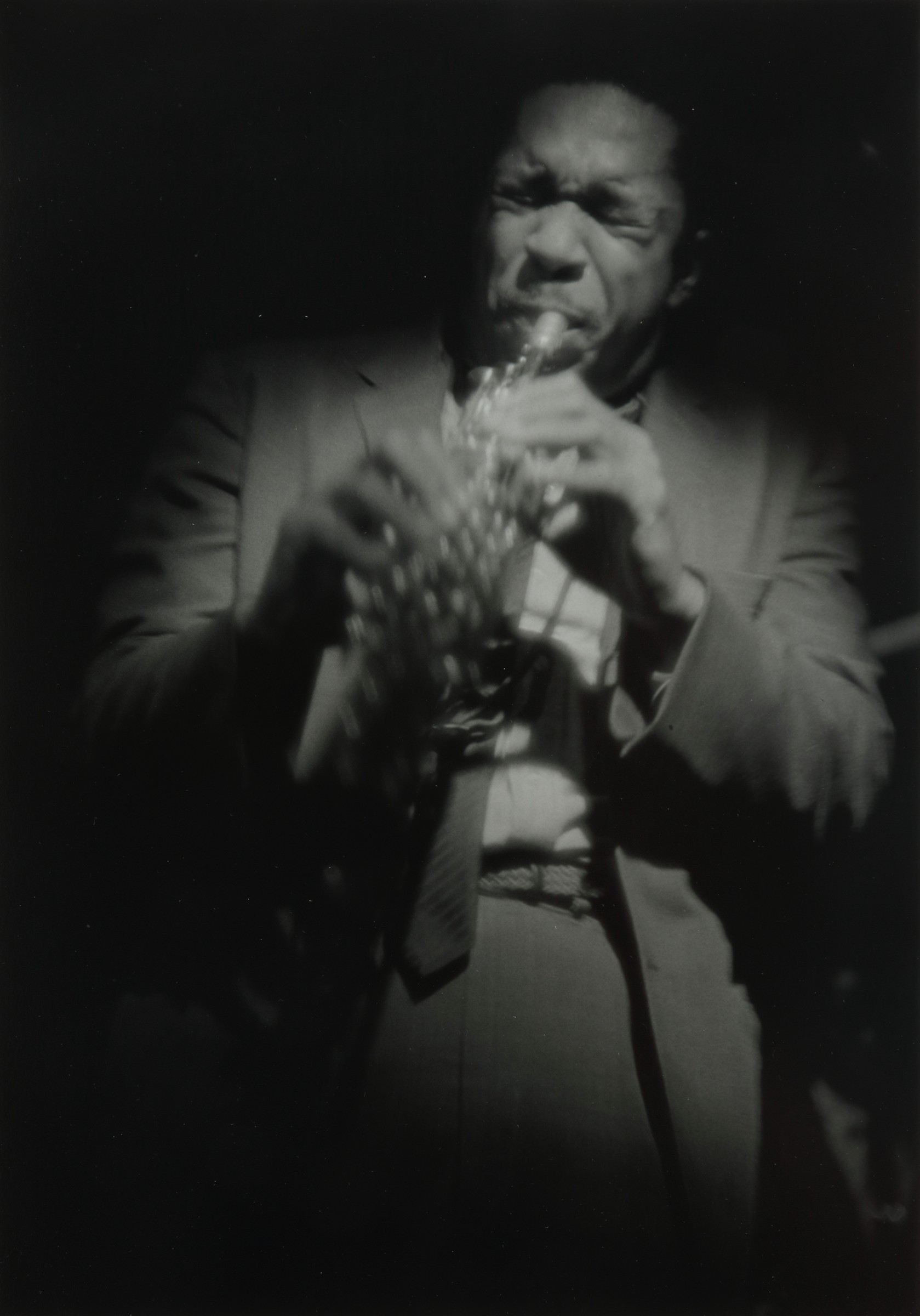 Photograph of John Coltrane playing a saxophone and moving around.