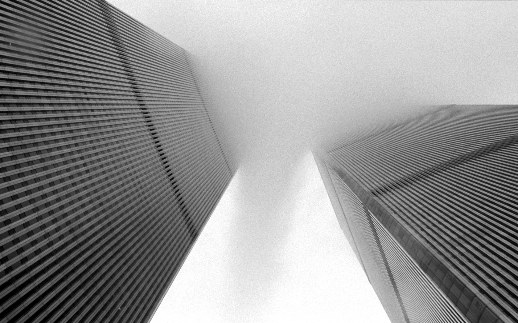 A view of the Twin Towers looking up between the two buildings, partially obscured by clouds