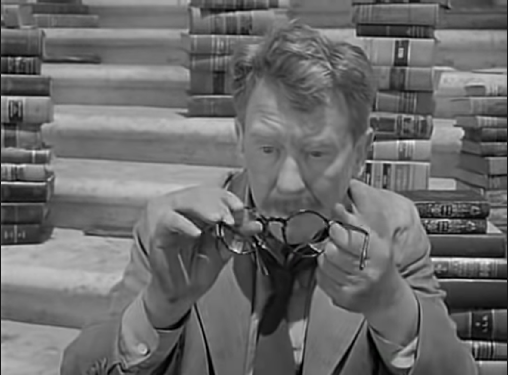 """Screenshot of 1959's Twilight Zone episode """"Time Enough at Last"""", showing Henry Bemis holding his broken glasses amid books."""