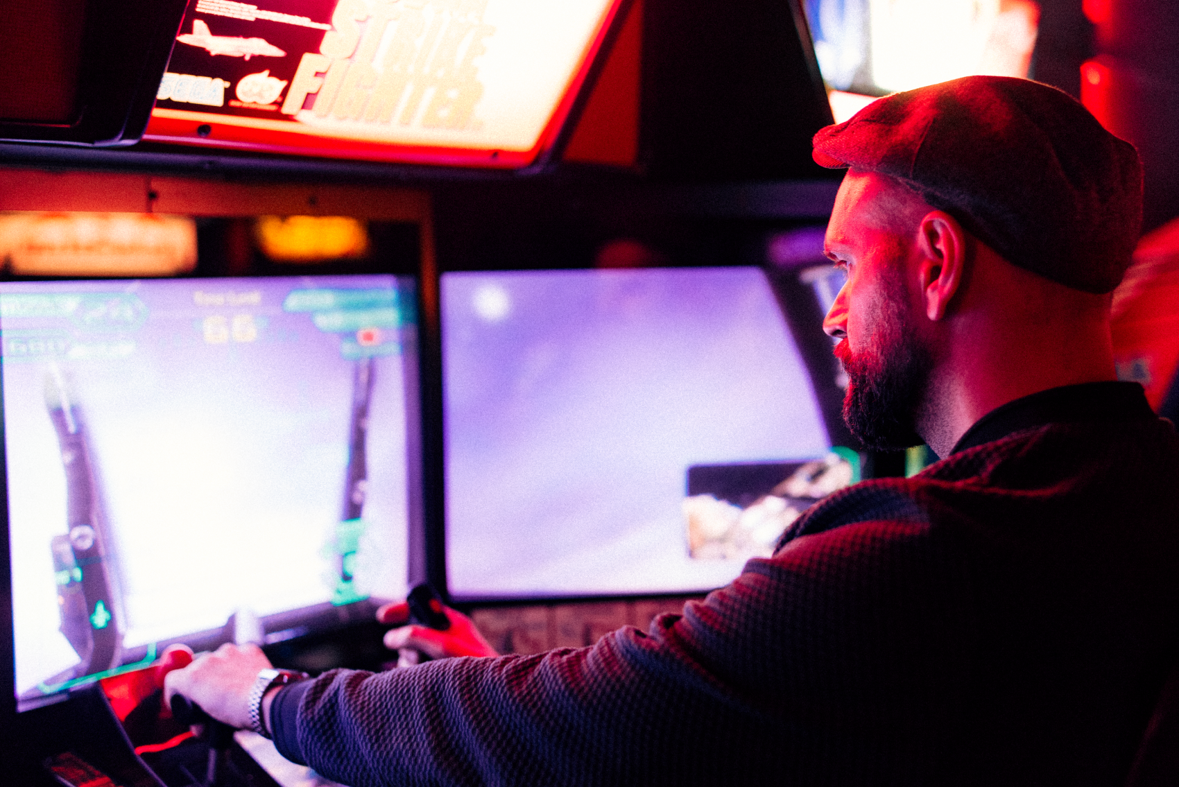 A man in a hat playing a first person shooter game at an arcade.