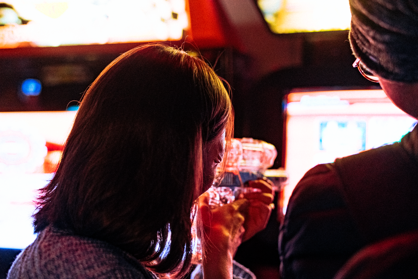 A woman playing a shooting game at an arcade