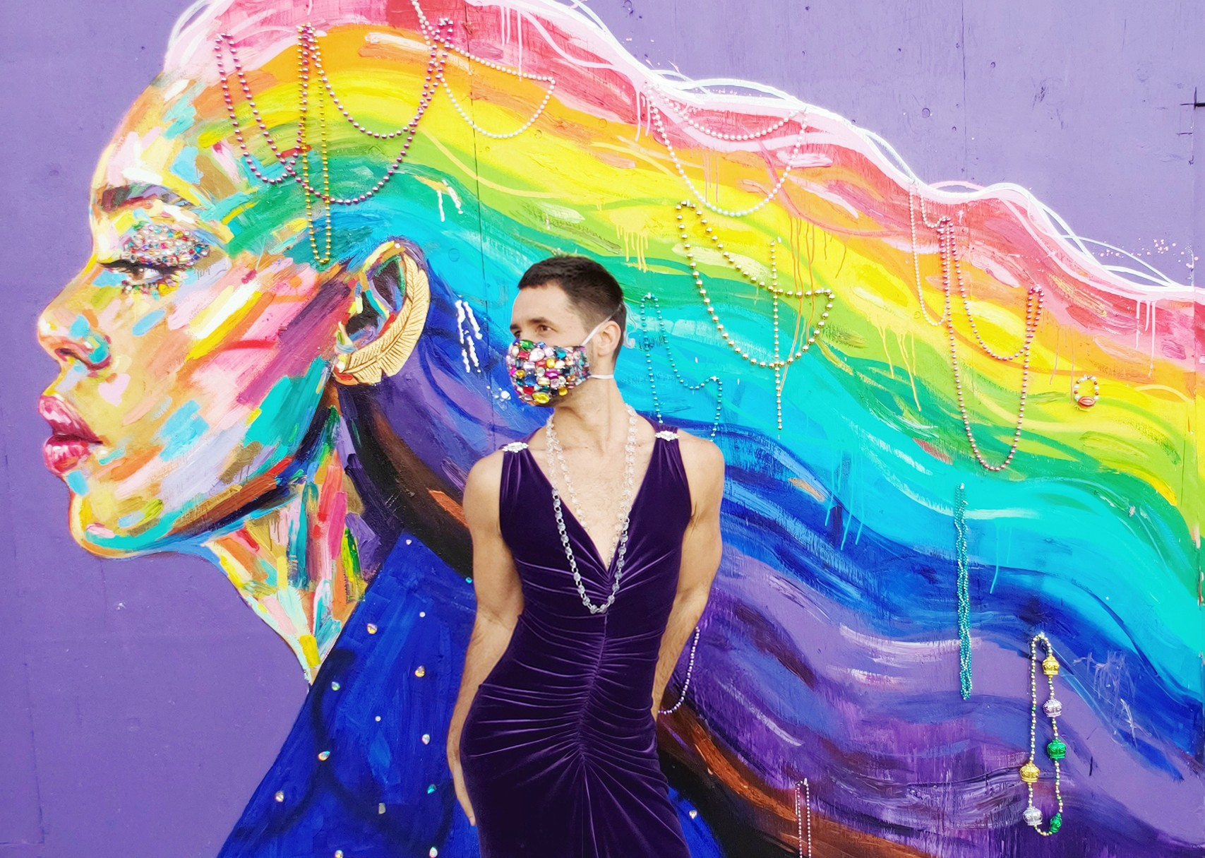 A person wearing a jeweled face mask posing in a sleeveless dark-purple dress in front of a rainbow mural of Laverne Cox.