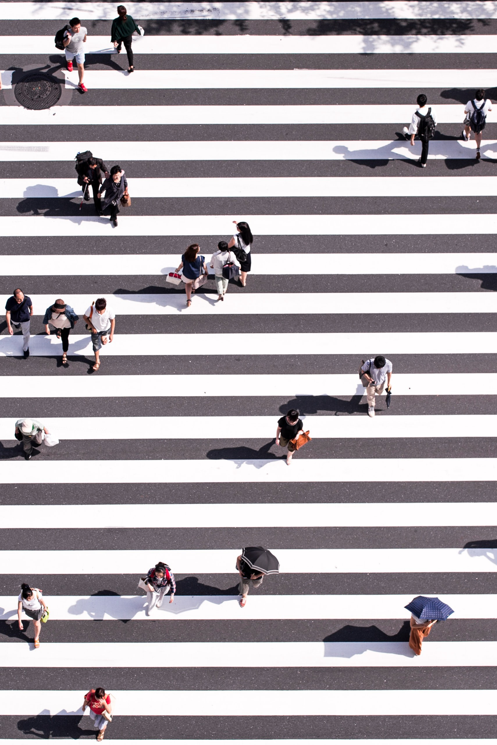 Aerial view of people crossing a black-and-white crosswalk.