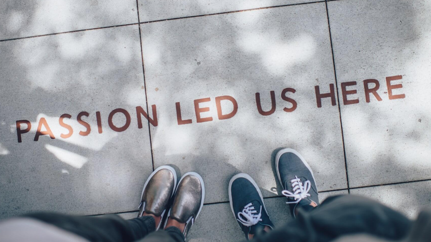 'Passion led us here' painted on the ground in front of two people's feet