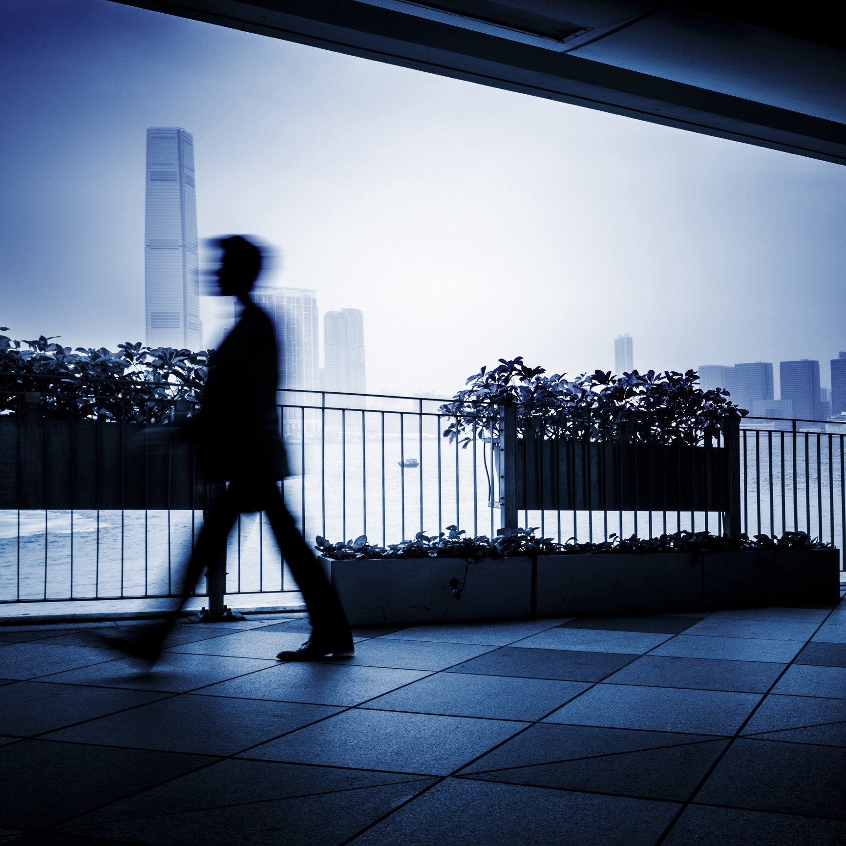 A blurry image of a man walking across an outdoor balcony space. There are tall buildings in the background.