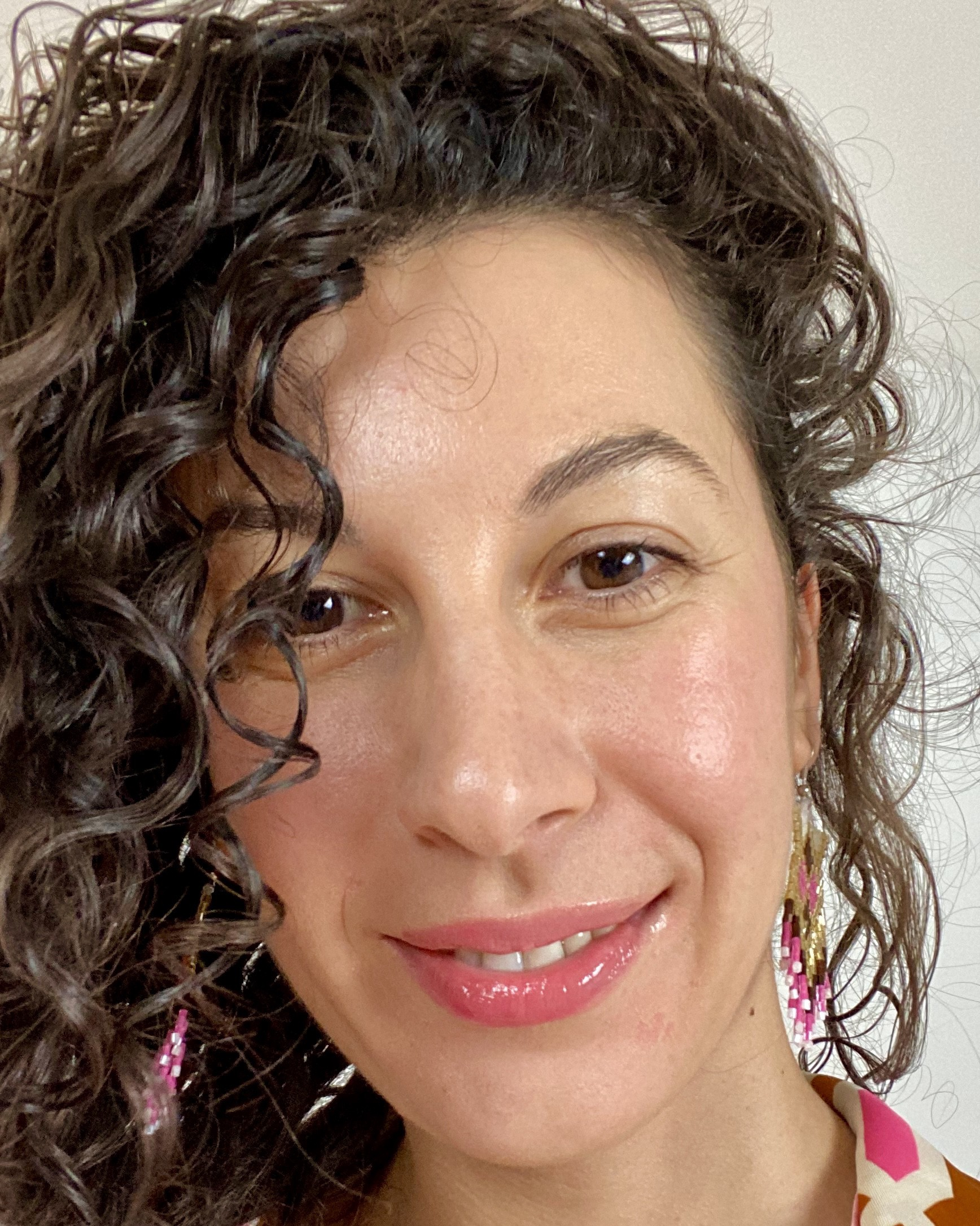 picture of the author smiling at the camera very close, curly hair